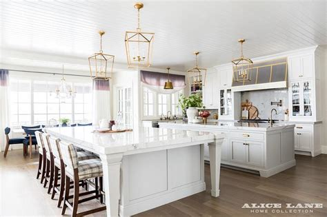 kitchen with center island two kitchen islands unified with brass lanterns