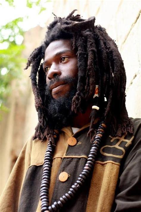 rasta for dreads a with a beard and thick dreadlocks gazes