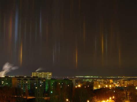 light pillars are descending to earth through eerie light pillars