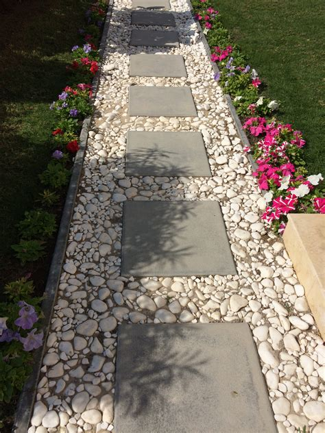 pathway designs cement block tiles bordered by white pebbles for a simple