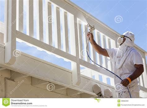 spray painting house house painter spray painting a deck of a home stock photo