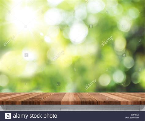 empty brown wood table top with sun and blur green tree