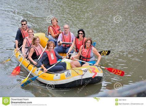 People On A Boat by Rafting Smiling Happy People On A Rubber Boat Rafting On