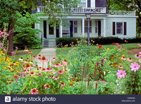 White Clapboard House With Cottage Garden Leading To Front