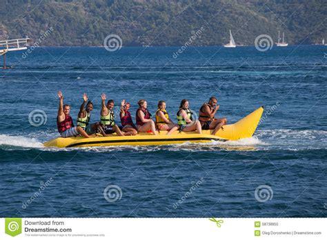 Banana Boat Group by Group Of Young People Riding Banana Boat Editorial Image